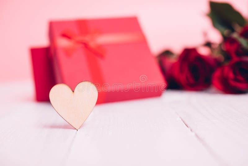 O coração de madeira em de madeira branco tem rosas da flor e o fundo vermelhos da caixa de presente imagem de stock