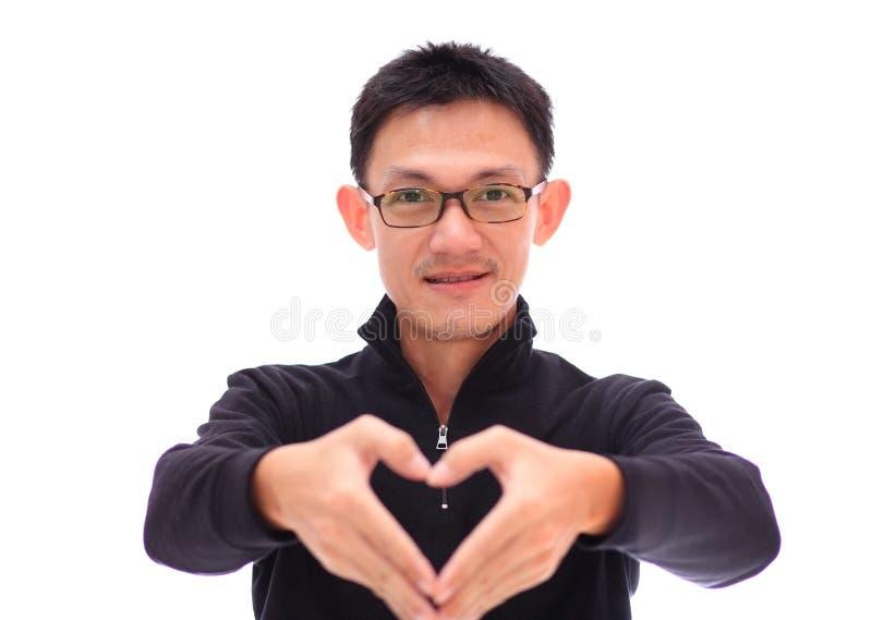 O coração de sorriso da mão do homem, homem novo atrativo faz o usin do coração imagem de stock royalty free