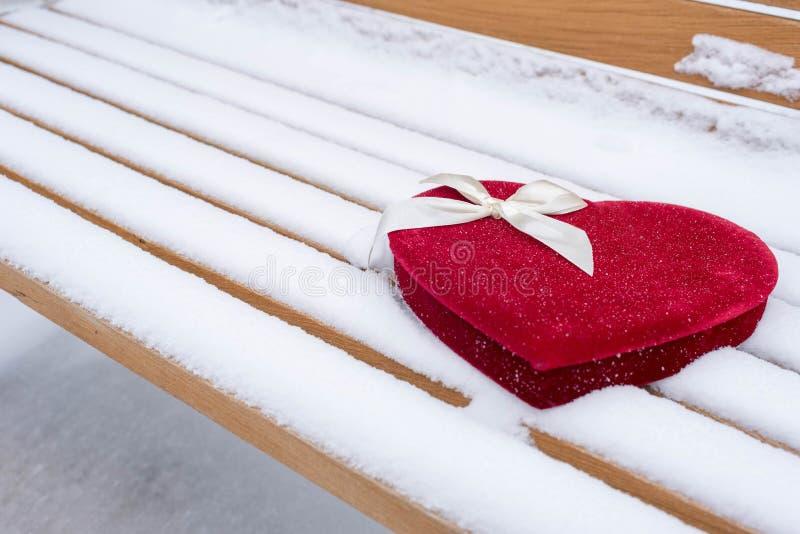 O coração de veludo deu forma à caixa dos doces em um banco de parque na neve imagens de stock