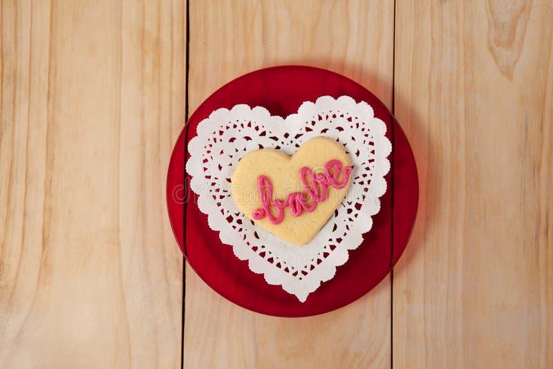 O coração deu forma à cookie congelada com creme cor-de-rosa no borracho do texto foto de stock royalty free