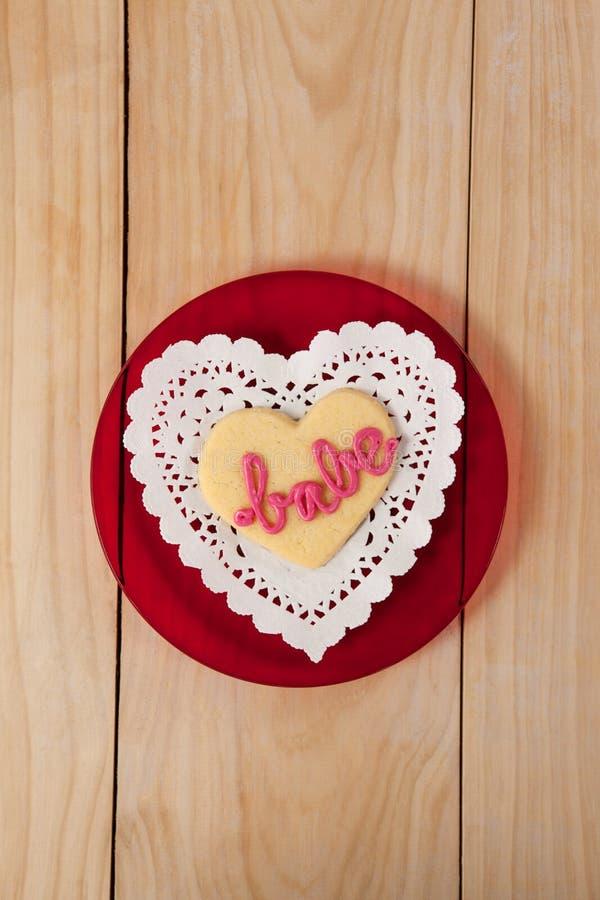 O coração deu forma à cookie congelada com creme cor-de-rosa no borracho do texto fotos de stock