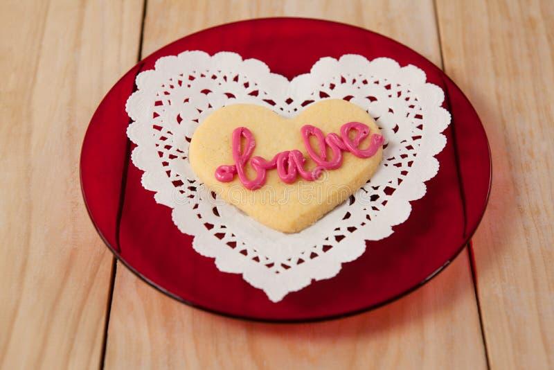 O coração deu forma à cookie congelada com creme cor-de-rosa no borracho do texto fotos de stock royalty free