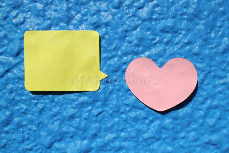 O coração deu forma à nota da etiqueta na parede azul foto de stock royalty free