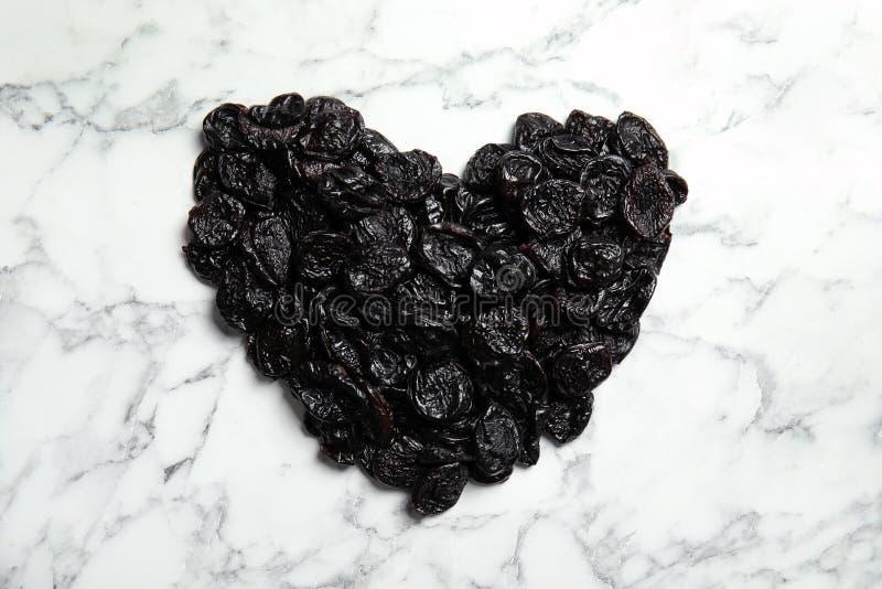 O coração deu forma à pilha de ameixas secadas doces no fundo de mármore, vista superior fotografia de stock royalty free