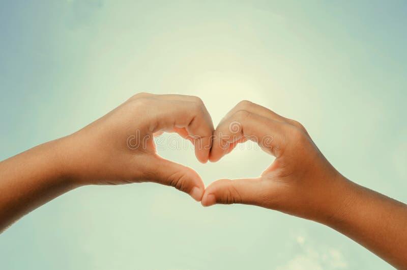 O coração deu forma às mãos com instagram do sol e do céu do meio-dia imagem de stock royalty free