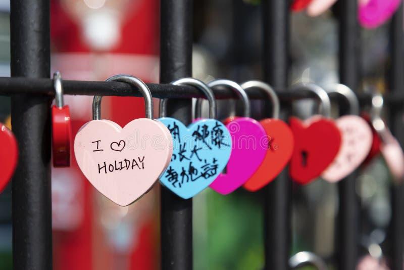 O coração deu forma ao cadeado do amor na cerca que simboliza uma união forte imagens de stock royalty free