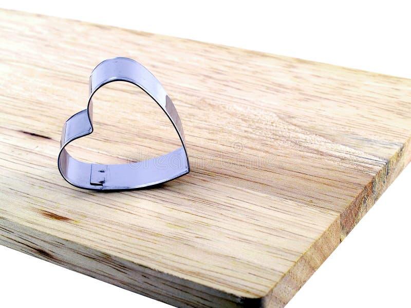 O coração deu forma ao cortador das cookies na placa de corte de madeira fotografia de stock