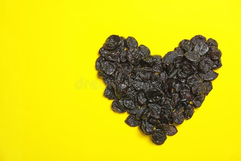 O coração deu forma ao montão de ameixas secas saborosos no fundo da cor, vista superior com espaço para o texto Frutos secos com fotos de stock royalty free