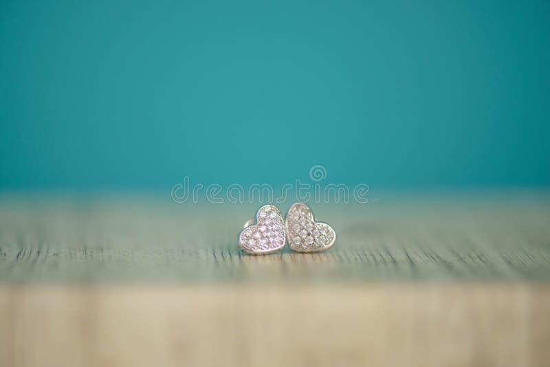 O coração deu forma aos pares de prata de brincos com os diamantes genuínos ou do falso fotografia de stock