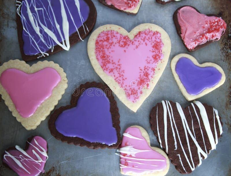 O coração deu forma a cookies da baunilha e do chocolate com rosa e à crosta de gelo roxa para o dia de Valentim na folha de cook fotografia de stock