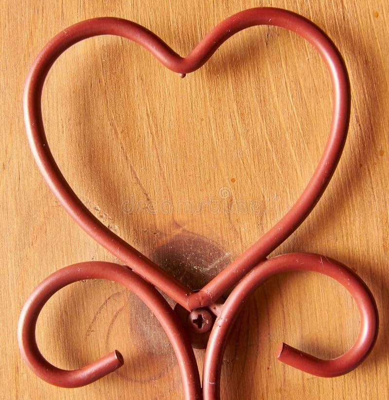 O coração deu forma do fio de metal marrom com fundo de madeira imagem de stock