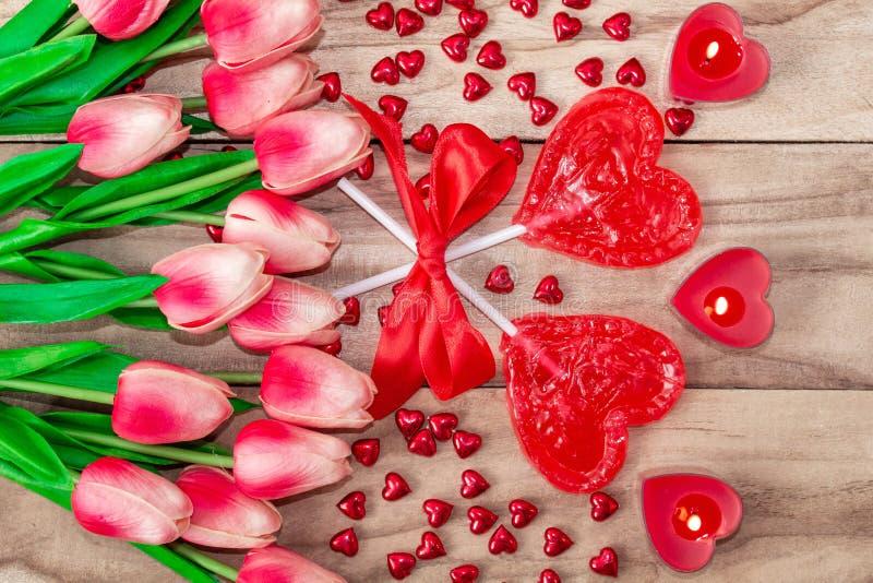 O coração deu forma a pirulitos no fundo de madeira com coração deu forma às velas alinhadas com flores das tulipas Fundo festivo imagens de stock royalty free
