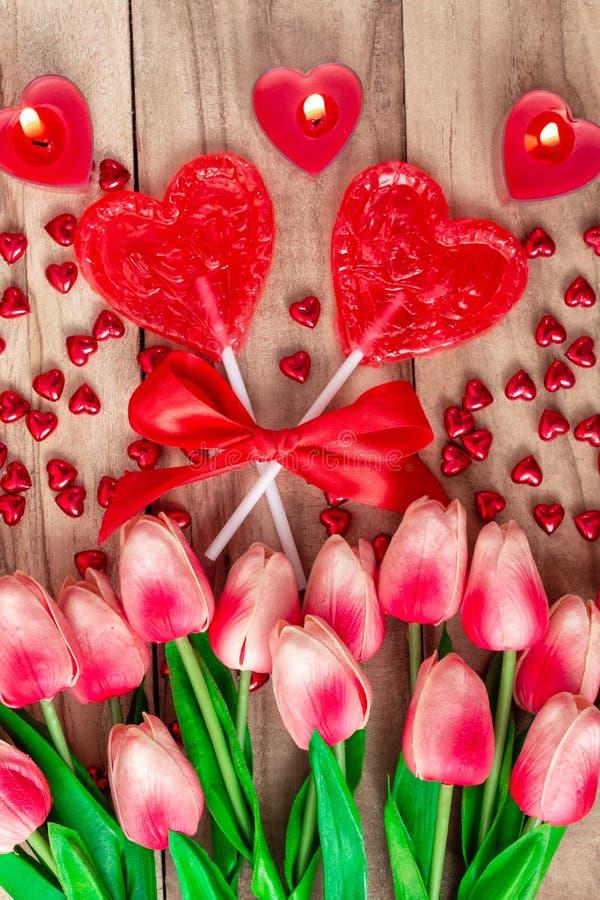 O coração deu forma a pirulitos no fundo de madeira com coração deu forma às velas alinhadas com flores das tulipas Fundo festivo fotografia de stock
