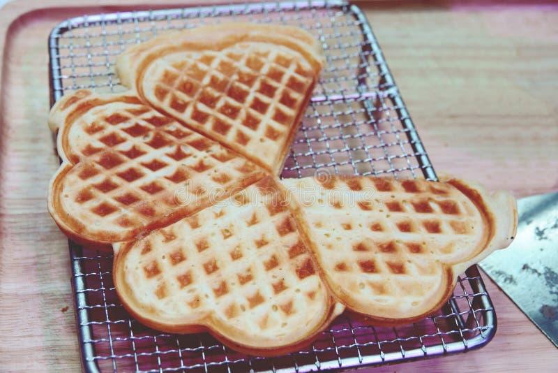 O coração deu forma a waffles no fundo de madeira da tabela imagem de stock