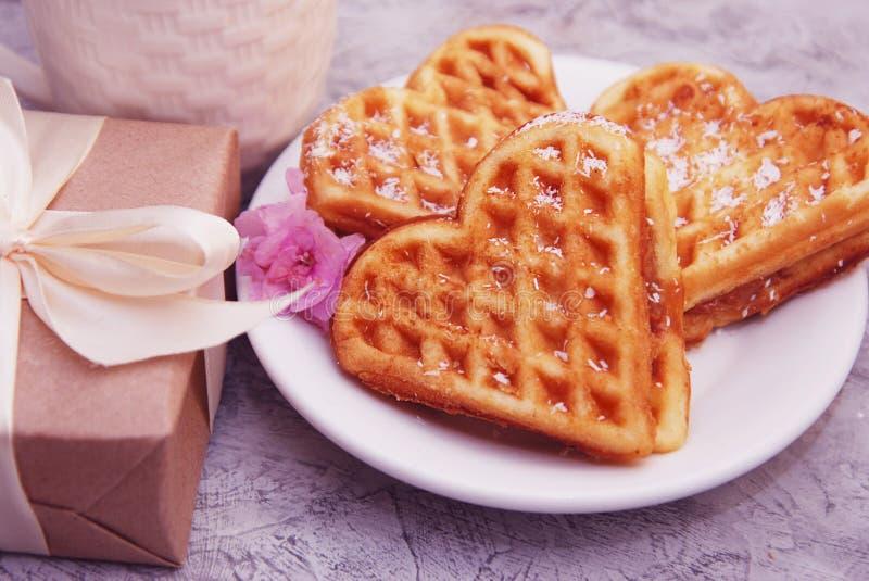 O coração deu forma a waffles para o café da manhã com a caixa de presente na tabela com pouca flor cor-de-rosa, vista de cima de imagens de stock