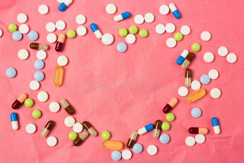 O coração do espaço vazio deu forma ao quadro para o texto com comprimidos da cor, comprimidos e cápsulas fotos de stock