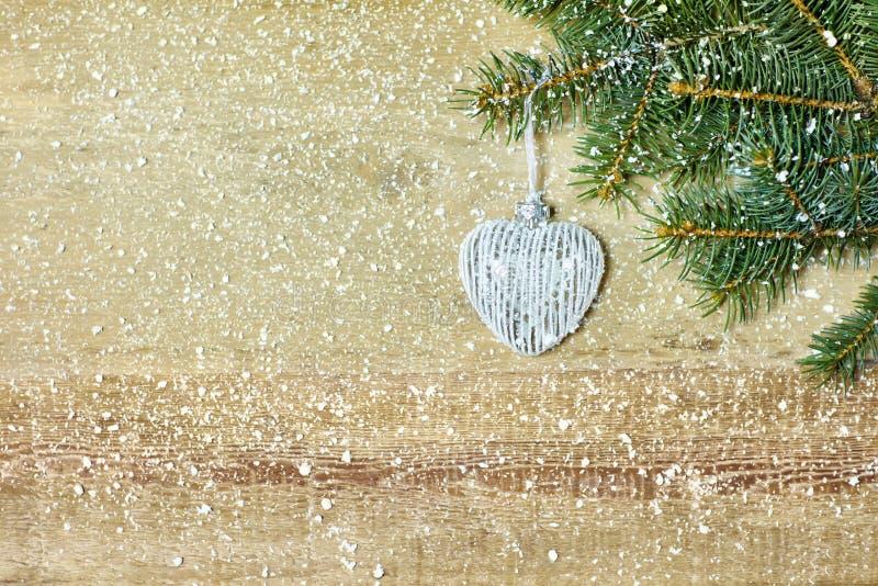 O coração do Natal deu forma à bola no branche da árvore de abeto fotos de stock royalty free