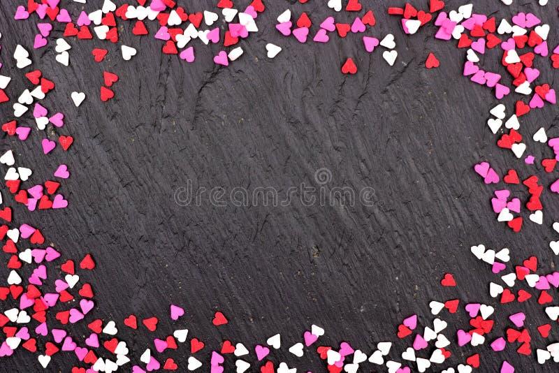 O coração dos doces do dia de Valentim polvilha o quadro sobre um fundo preto fotos de stock
