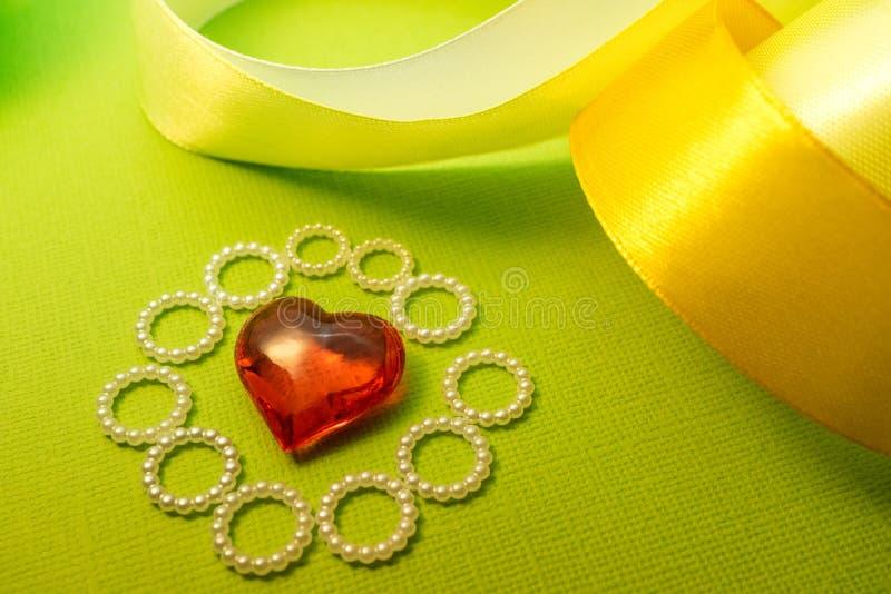 O coração e a fita em um fundo verde projetam para mensagens do amor, cumprimentos imagem de stock royalty free