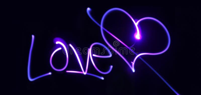 O coração e a inscrição de néon amam em um fundo escuro foto de stock royalty free