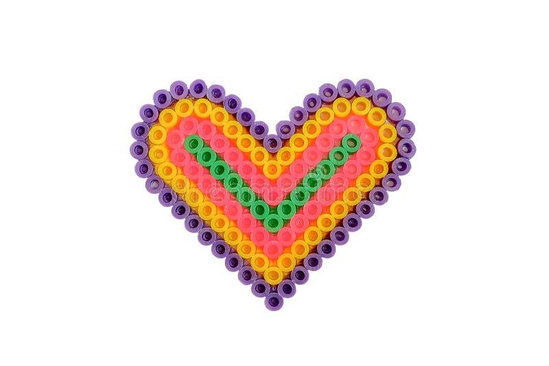O coração feito a mão do applique deu forma feito dos tubos isolados no branco imagem de stock