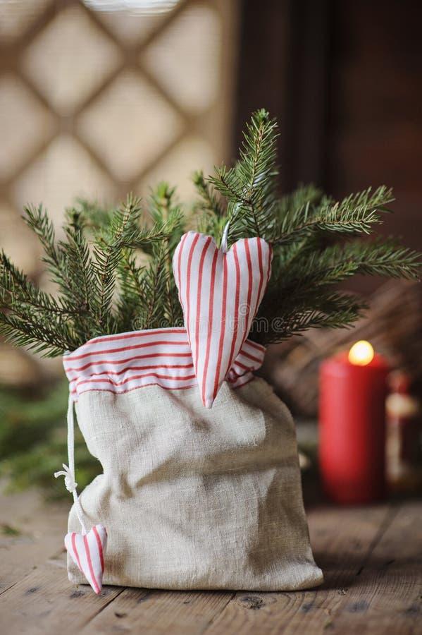 O coração feito a mão do Natal deu forma à decoração e aos pinhos no saco foto de stock royalty free