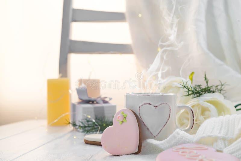 O coração festivo deu forma a cookies com a vitrificação colorida e a xícara de café em uma tabela de madeira com espaço da cópia fotos de stock