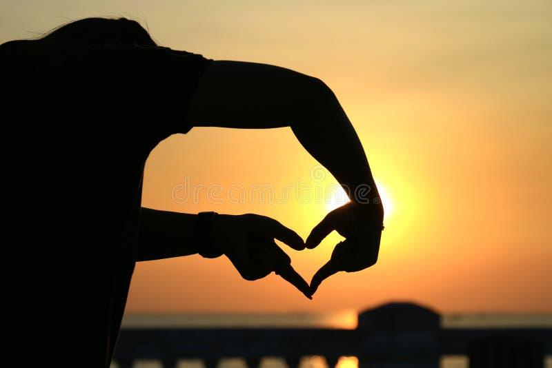 O coração fez as mãos que formam a forma do coração com a silhueta do por do sol do ouro, sombra da mulher o amor da mão que assi imagens de stock