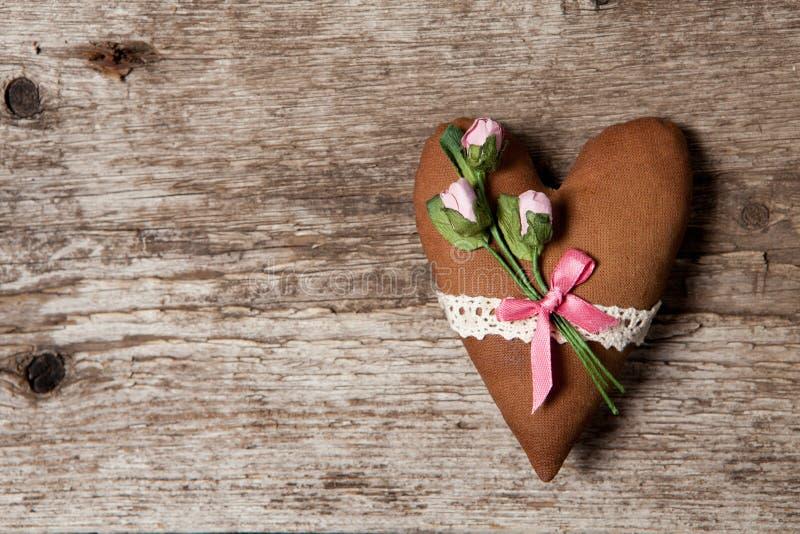 O coração macio fez do pano com rosas cor-de-rosa em um fundo de madeira imagens de stock