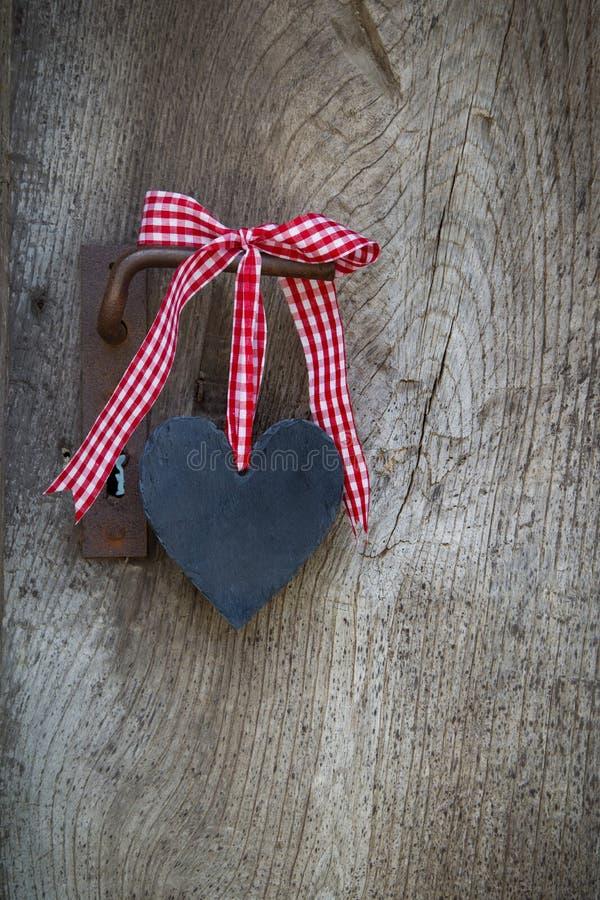 O coração preto com um branco vermelho verificou a fita que pendura em um velho faz imagens de stock royalty free