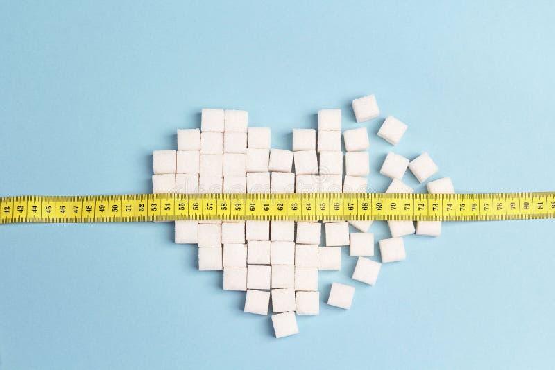 O coração quebrado fez de cubos do açúcar com medida da fita em um CCB azul fotografia de stock