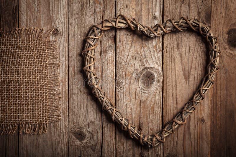 O coração rústico deu forma a ramos e a juta em uma tabela de madeira velha imagem de stock
