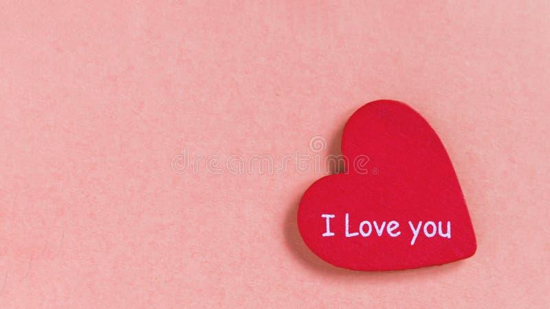 O coração vermelho com texto ama-o no fundo cor-de-rosa fotos de stock royalty free