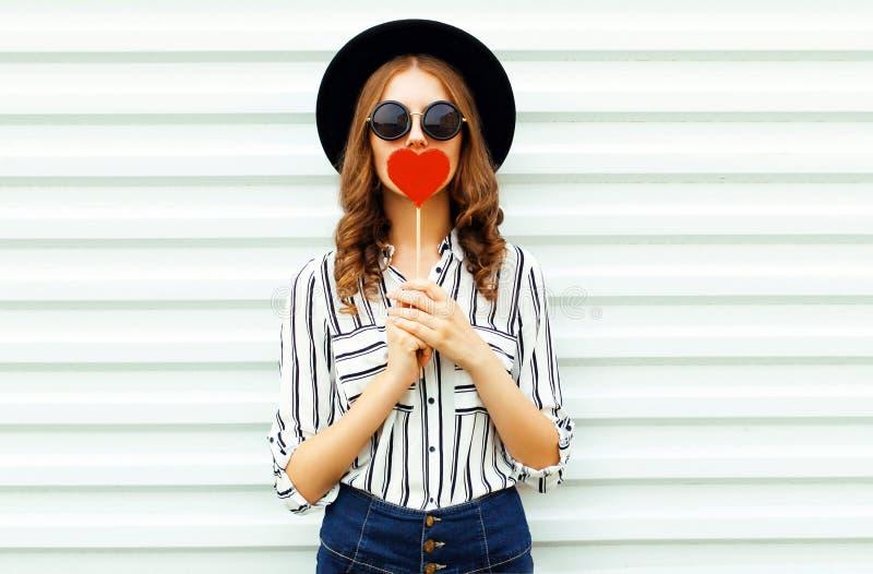 O coração vermelho de beijo da jovem mulher do retrato deu forma ao pirulito ou esconde seus bordos no chapéu redondo preto, cami fotografia de stock royalty free