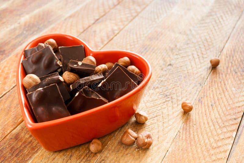 O coração vermelho deu forma à bacia com partes do chocolate e o diago de encontro nuts fotografia de stock royalty free