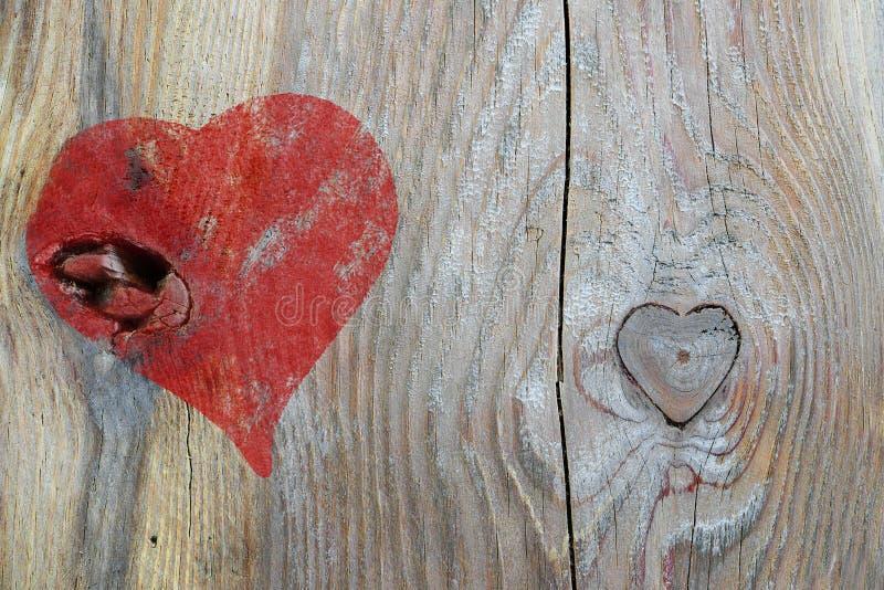 O coração vermelho pintado na madeira e o knothole no coração dão forma, amam para trás foto de stock royalty free