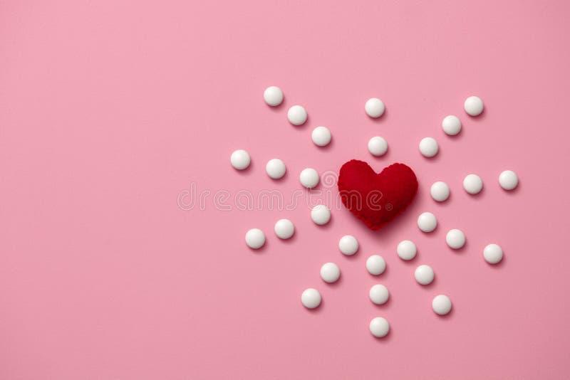 O coração vermelho sentiu mentiras em um fundo cor-de-rosa tratamento dos pacientes com doença cardíaca um símbolo da saúde do co imagens de stock royalty free