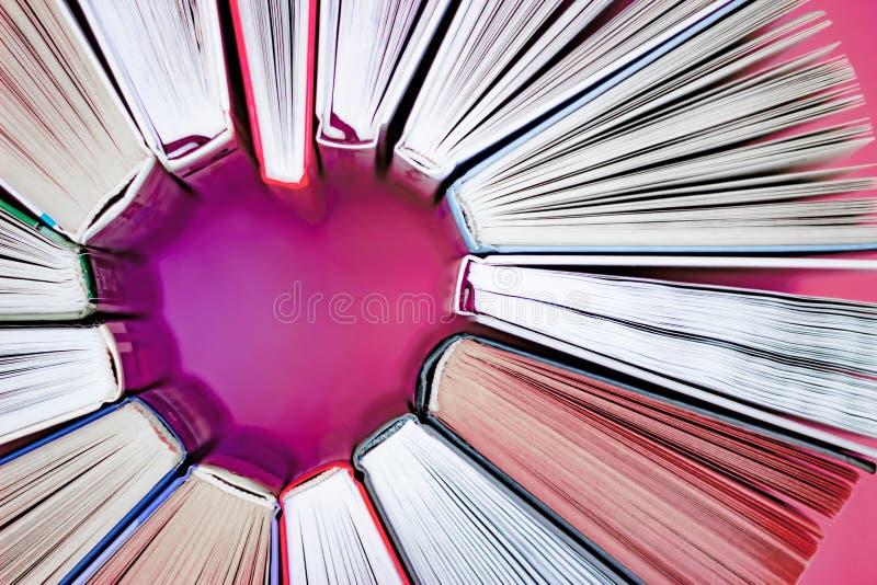 O cora??o dos livros no fundo cor-de-rosa Vista superior Leitura do amor imagem de stock