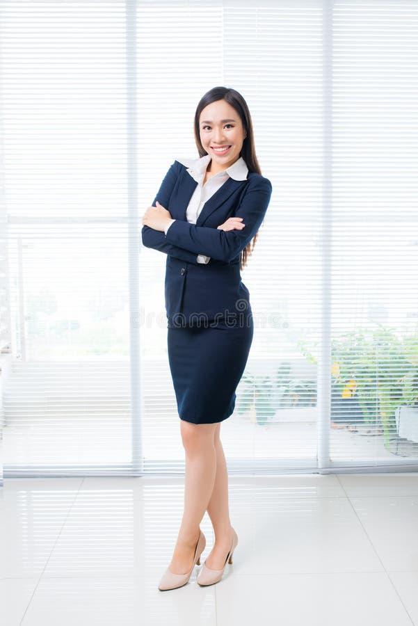 O corpo completo disparou da mulher de negócios asiática segura que está no offi fotografia de stock