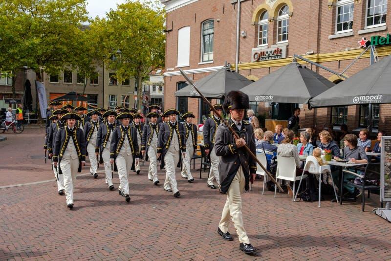 O corpo do pífano e de cilindro de Grey Coats está marchando através das ruas da louça de Delft fotografia de stock royalty free