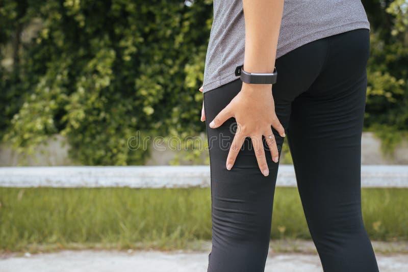 O corredor asiático da mulher que sofre da dor nos pés seja ferido, mão que toca em sua coxa do músculo após movimentar-se no cor fotografia de stock royalty free