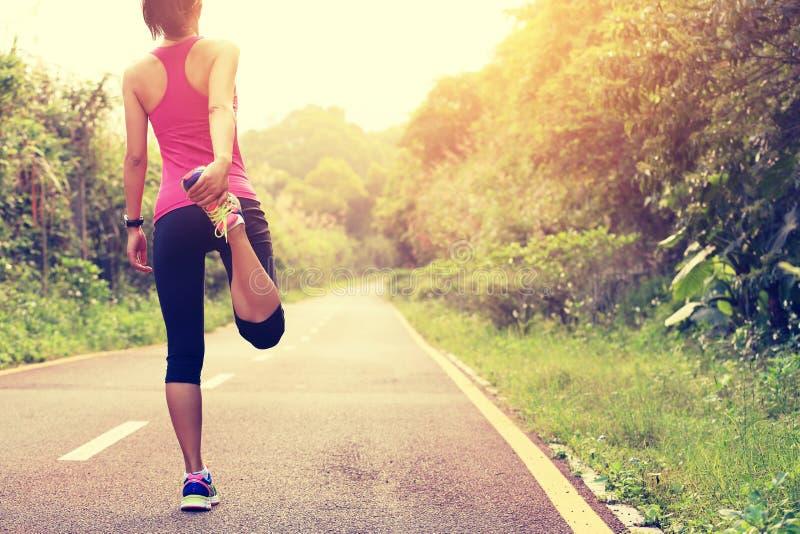 O corredor da jovem mulher aquece-se fotografia de stock royalty free