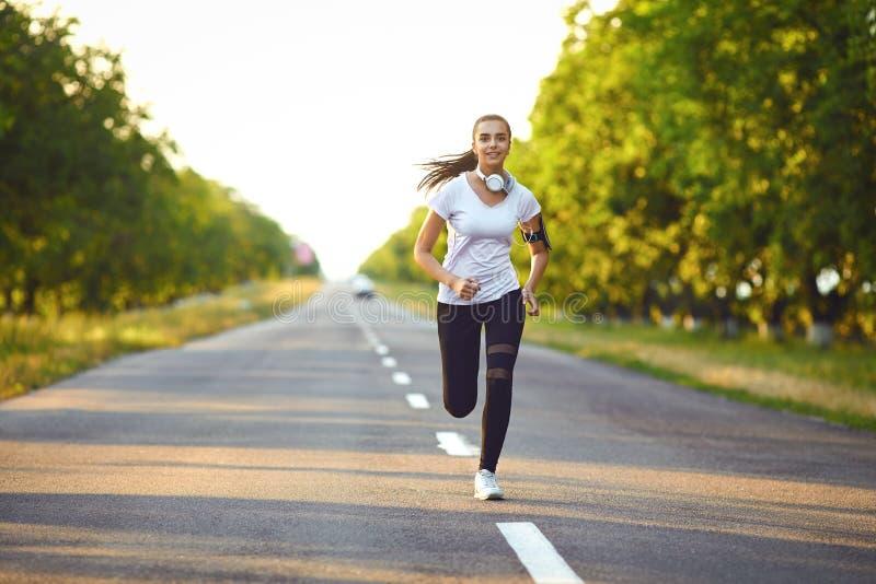 O corredor da menina corre ao longo da estrada no verão fotografia de stock royalty free