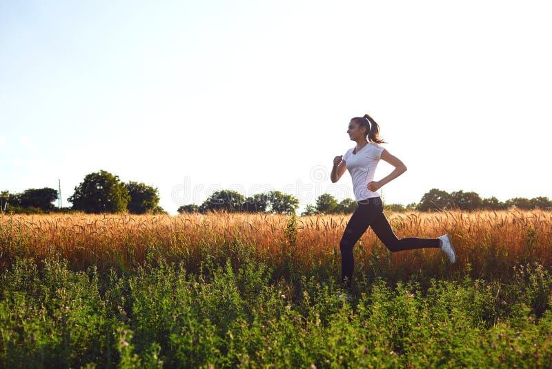O corredor da menina corre ao longo da estrada no verão fotos de stock