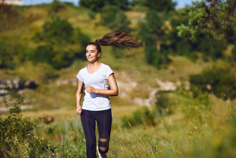 O corredor da menina corre avante na natureza no verão foto de stock