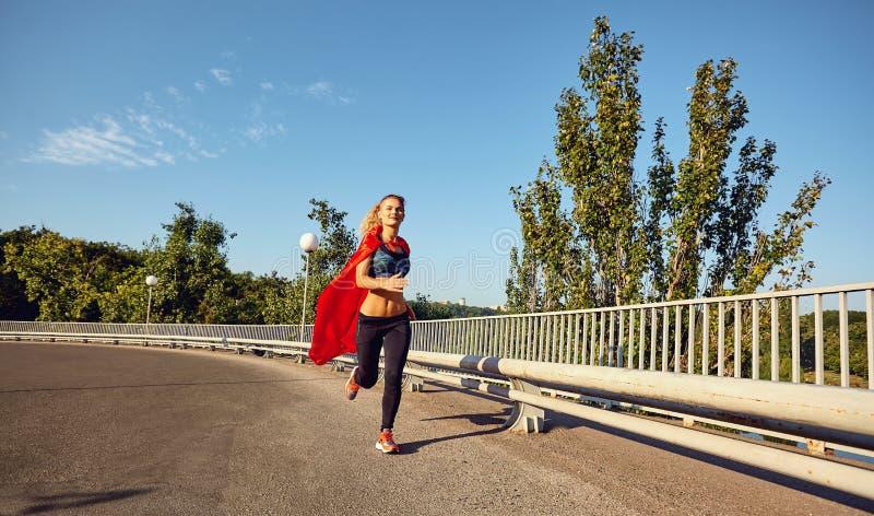 O corredor da menina em um traje do super-herói corre ao longo da estrada no ci foto de stock