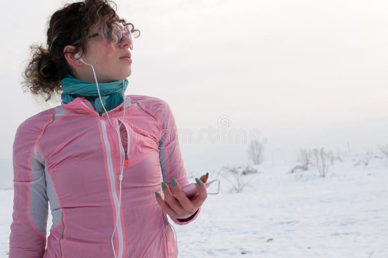O corredor da menina escuta música do smartphone no dia de inverno imagem de stock royalty free