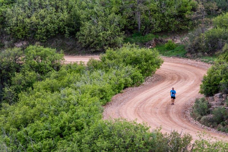 O corredor do homem em piques da estrada da montanha da sujeira repica a cordilheira Colorado Springs imagem de stock royalty free