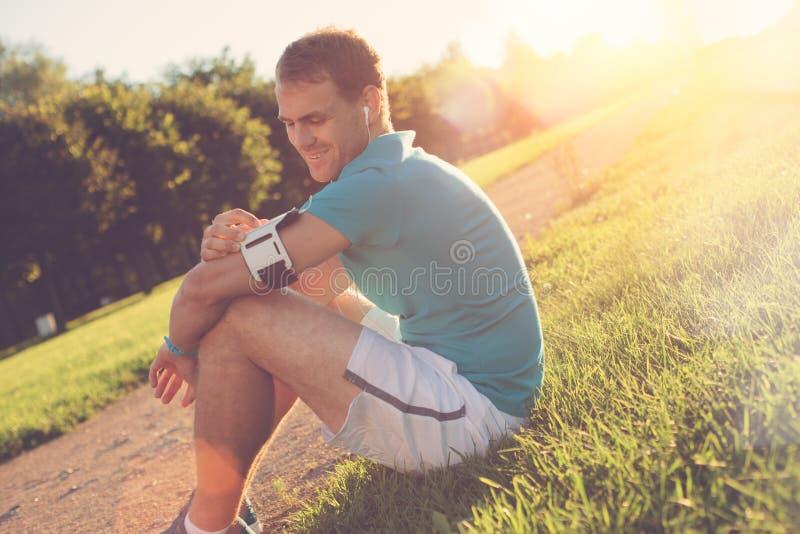 O corredor feliz que verifica seu treinamento resulta no smartphone fotografia de stock royalty free