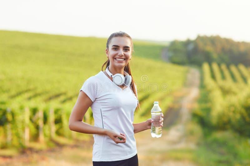 O corredor moreno da menina com uma garrafa da água está no treinamento imagens de stock